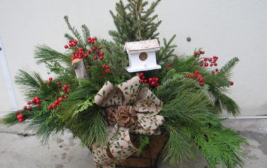 Bouquet of green spruce tops with holly and a white bird house